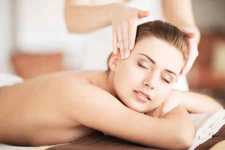 beauty and spa concept - beautiful woman in spa salon getting massage photo