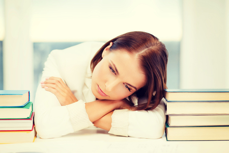 business, education, people concept - tired businesswoman or student with pile of books and notes studying indoors photo