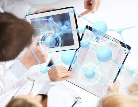 healthcare, technology, medicine and people concept - group of doctors with tablet pc, clipboard and molecular projection Archivio Fotografico