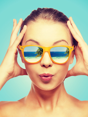 travel, vacation, summer holidays and happy people concept - portrait of amazed teenage girl in sunglasses with beach reflection Stockfoto