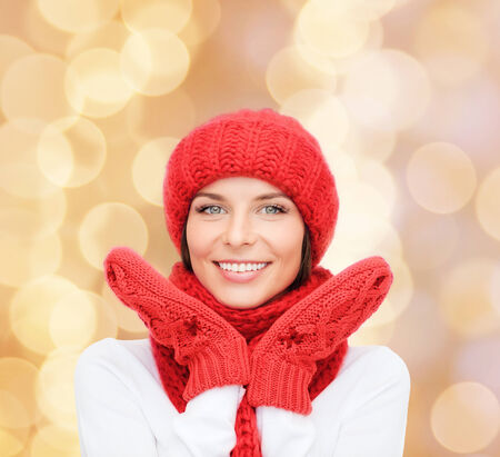 winter woman: happiness, winter holidays, christmas and people concept - smiling young woman in red hat, scarf and mittens over beige lights background