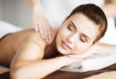 wellness center: beauty and spa concept - woman in spa salon getting massage