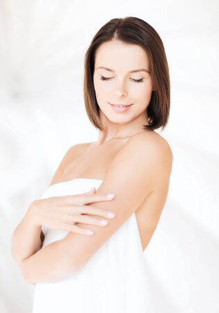 smooth skin: beauty, spa and people concept - beautiful woman standing in towel