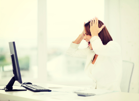 business, problem, crisis, stress and education concept - stressed businesswoman with computer at work photo