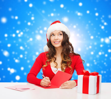 christmas, holidays, celebration, greeting and people concept - smiling woman in santa helper hat with gift box writing letter or sending post card over blue snowy background photo