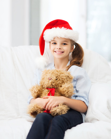 christmas, x-mas, winter, happiness concept - smiling girl in santa helper hat with teddy bear at home photo
