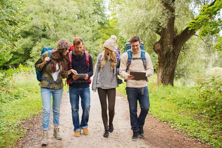 adventure, travel, tourism, hike and people concept - group of smiling friends with backpacks and tablet pc computer walking outdoors photo