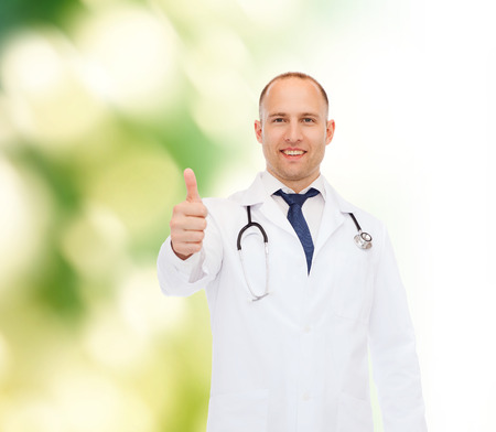 approvement: healthcare, profession, gesture and medicine concept - smiling male doctor with stethoscope showing thumbs up over nature background Stock Photo