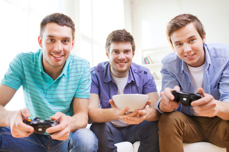 out of control: friendship, technology, games and home concept - smiling male friends playing video games at home