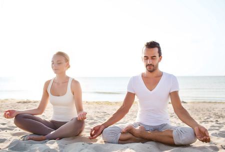 fitness, sport, friendship and lifestyle concept - smiling couple making yoga exercises sitting on sand outdoors
