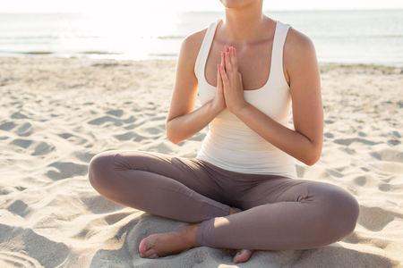 fitness, sport, people and lifestyle concept - close up of woman making yoga exercises on pier outdoors photo