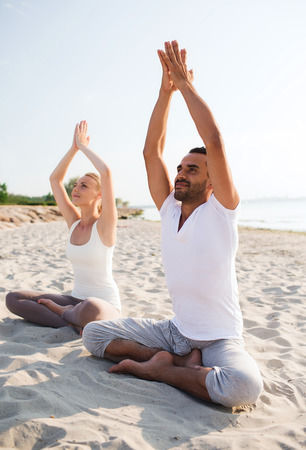 fitness, sport, friendship and lifestyle concept - smiling couple making yoga exercises sitting on sand outdoors photo