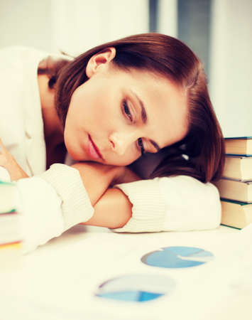 education and business concept - bored young woman with many books and graphs indoors photo