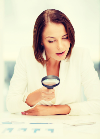 business, education, people concept - businesswoman or student in eyeglasses working with graphs in office photo