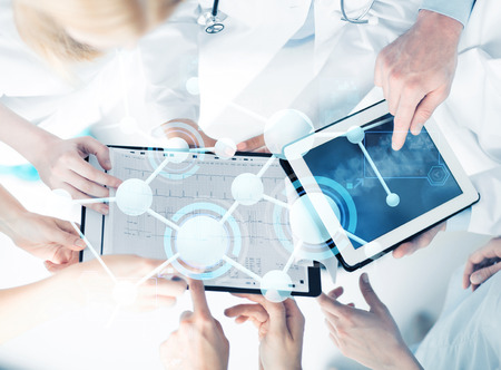 healthcare, technology, medicine and people concept - group of doctors with tablet pc, clipboard and molecular projection Stock Photo