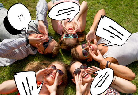 friendship, leisure, summer and people concept - group of smiling friends lying on grass in circle outdoors photo
