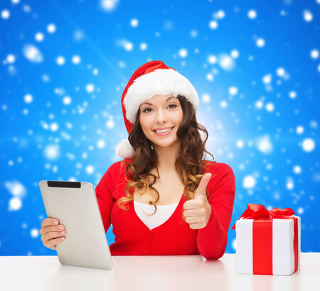 approvement: christmas, holidays, technology, gesture and people concept - smiling woman in santa helper hat with gift box and tablet pc computer showing thumbs up over blue snowy background