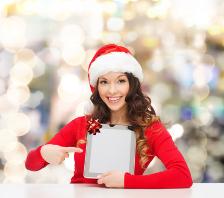 christmas, holidays, technology and people concept - smiling woman in santa helper hat with tablet pc computer over lights background photo