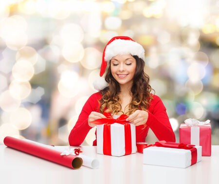 christmas wrapping: christmas, holidays, celebration, decoration and people concept - smiling woman in santa helper hat with decorating paper packing gift boxes over lights background
