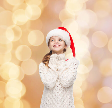 christmas, holidays, childhood and people concept - smiling girl in santa helper hat over beige lights background photo