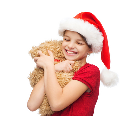christmas, x-mas, winter, happiness concept - smiling girl in santa helper hat with teddy bear photo