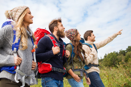 expedition: adventure, travel, tourism, hike and people concept - group of smiling friends walking with backpacks Stock Photo