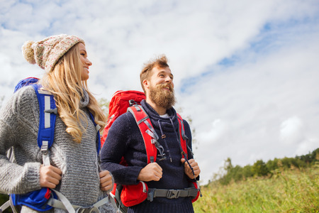 expedition: adventure, travel, tourism, hike and people concept - smiling couple walking with backpacks outdoors