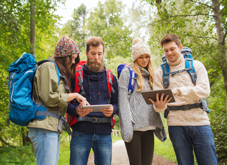 adventure, travel, tourism, hike and people concept - group of smiling friends with backpacks and tablet pc computers outdoors photo