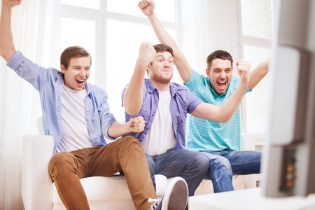 soccer fans: friendship, sports and entertainment concept - happy male friends supporting football team at home