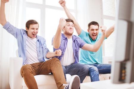 personas viendo television: la amistad, el deporte y el concepto de entretenimiento - amigos hombres felices que apoyan equipo de fútbol en casa Foto de archivo