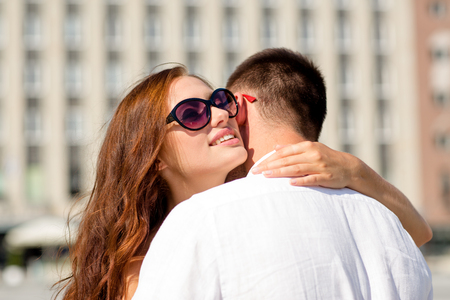 love, wedding, summer, dating and people concept - smiling couple wearing sunglasses hugging in city photo