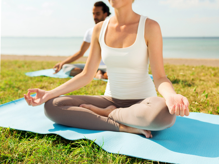 fitness, sport, people and lifestyle concept - close up of couple making yoga exercises sitting on mats outdoors photo