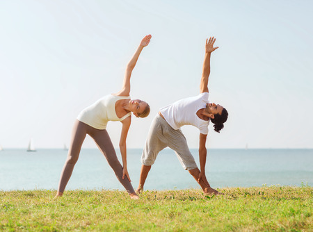 fitness, sport, friendship and lifestyle concept - couple making yoga exercises outdoors photo