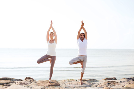 women and men: fitness, sport, friendship and lifestyle concept - couple making yoga exercises on beach