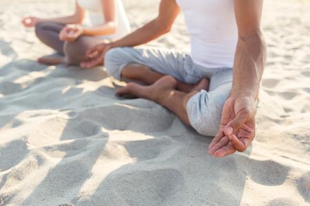 mujer meditando: fitness, deporte, la gente y el estilo de vida concepto - Cierre de ejercicios de yoga par hacer que se sientan en el muelle al aire libre Foto de archivo