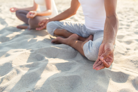 yoga meditation: fitness, sport, people and lifestyle concept - close up of couple making yoga exercises sitting on pier outdoors