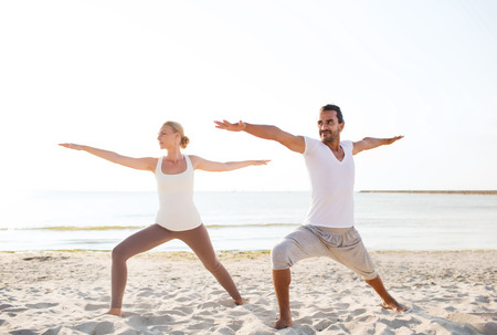 fitness, sport, friendship and lifestyle concept - couple making yoga exercises on beach photo