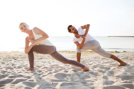 yoga beach: fitness, sport, friendship and lifestyle concept - couple making yoga exercises on beach