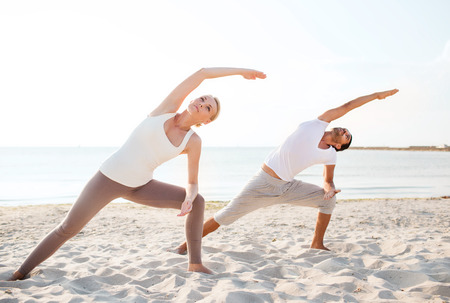 family exercise: fitness, sport, friendship and lifestyle concept - couple making yoga exercises on beach