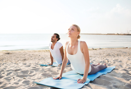 fitness, sport, friendship and lifestyle concept - couple making yoga exercises lying on mats outdoors photo