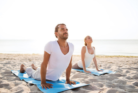 yoga: fitness, sport, friendship and lifestyle concept - couple making yoga exercises lying on mats outdoors