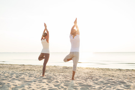 fitness, sport, people and lifestyle concept - couple making yoga exercises on sand outdoors from back photo