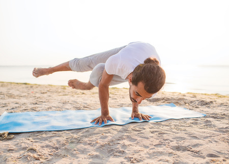 beach mat: fitness, sport, people and lifestyle concept - man doing yoga exercises on mat outdoors