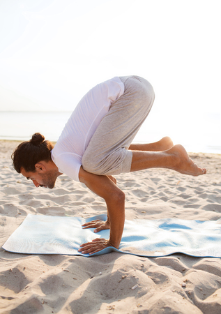 yoga beach: fitness, sport, people and lifestyle concept - man doing yoga exercises on mat outdoors
