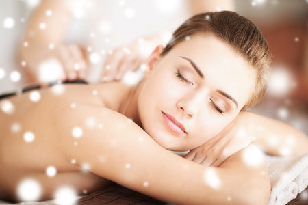 beauty parlor: health and beauty concept - woman in spa salon with hot stones