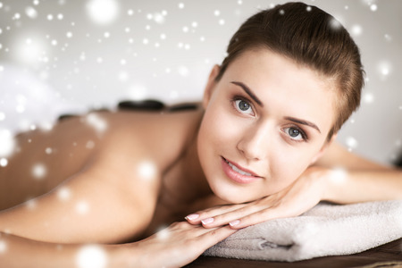 health and beauty concept - beautiful woman in spa salon with hot stones photo