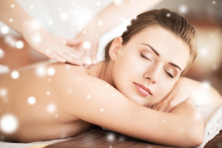 health and beauty concept - beautiful woman in spa salon getting massage photo