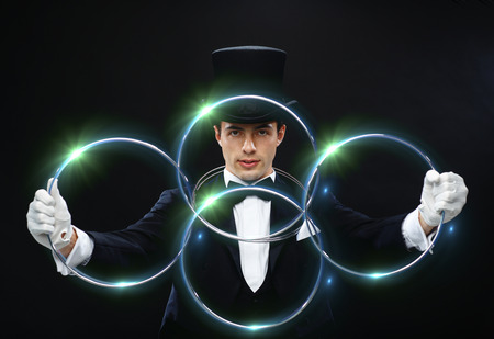 magic trick: magic, performance, circus, show concept - magician in top hat showing trick with linking rings