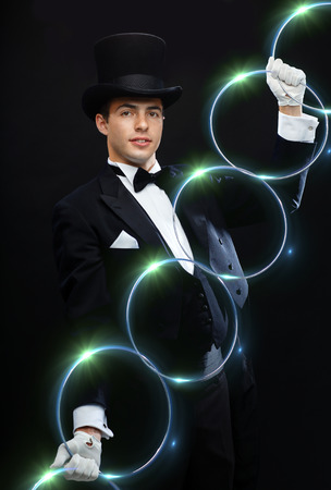 conjuring: magic, performance, circus, show concept - magician in top hat showing trick with linking rings
