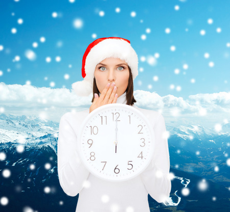 christmas, time, winter and people concept - smiling woman in santa helper hat with clock showing 12 over snowy mountains background photo